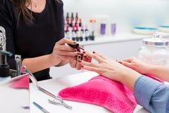 Nail saloon woman painting color nail polish in hands stock images