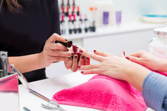 Nail saloon woman painting color nail polish in hands Royalty Free Stock Images