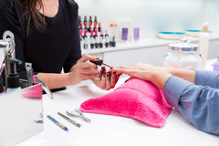 Nail saloon woman painting color nail polish in hands Royalty Free Stock Image
