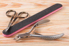 Nail scissors file and clippers to remove the cuticle care products on a light wooden background Stock Photography