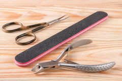 Nail scissors file and clippers to remove the cuticle care products on a light wooden background Royalty Free Stock Photo