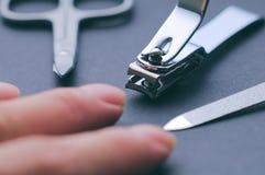 Nail Set and fingers. Closeup shot of nail set and fingers on grey Royalty Free Stock Photos