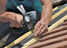 Nail slats on a roof. Close on hand of a roofer nailing slats on a roof for renovation Royalty Free Stock Photo