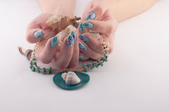 Nail, Spa and Shells. Female hands with beautiful painted nails and jewelry with shells on a white background royalty free stock photo