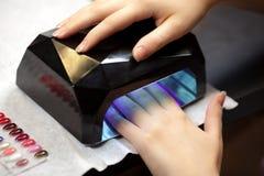 Nail studio. Woman's hands with UV lamps at nail studio Stock Photo