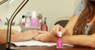 Nail technician applying nail varnish to customers nails stock footage