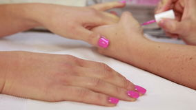 Nail technician applying pink varnish to customers nails stock footage