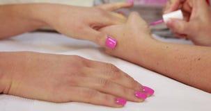 Nail technician applying pink varnish to customers nails stock footage
