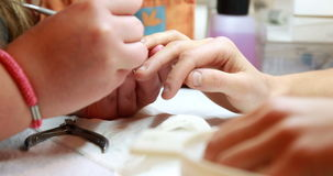 Nail technician giving customer a manicure stock footage