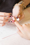 Nail technician applying nail template Stock Photography