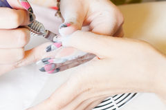 Nail technician sanding nails Royalty Free Stock Images