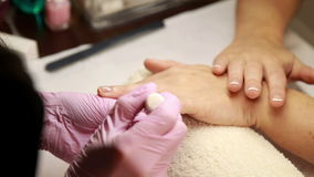Nail technician removing cuticles from customers nails stock video footage