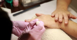 Nail technician removing cuticles from customers nails stock footage