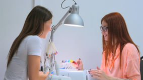 Nail technician shows the color palette of nail services in beauty salon royalty free stock photography