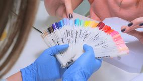 Nail technician shows the color palette of nail services in beauty salon royalty free stock photo