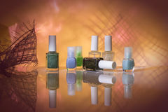 Nail varnish. Nail polish seven bottles with different shades on a lilac background Royalty Free Stock Photos