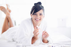 Nailcare. Pretty young woman in bathrobe looking at camera while taking care of her fingernails Stock Photography