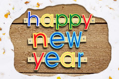 Nailed greeting text Happy New Year on woods in a snowy frame. Nailed greeting text Happy New Year on wooden background in a snowy frame stock photos