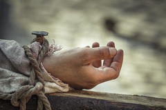 Nailed hand on cross. Closeup of hand nailed on wooden cross as reenactment of the crucifixion of Jesus Christ