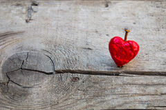 Nailed melting red love heart. On a wooden surface Royalty Free Stock Images