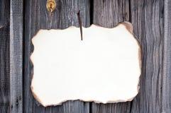 Nailed sheet of paper at wooden wall Royalty Free Stock Photos