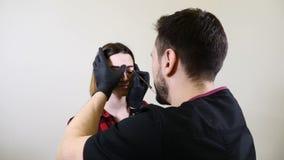 nailfile skönhet spikar den polerande salongen Manlig kosmetolog i svarta handskar som applicerar ögonbryneyeliner för det perman lager videofilmer