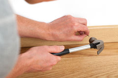 Nailing with hammer. Handyman repairing a skirting board on the floor Stock Images