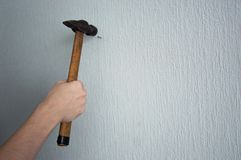 Knocking a nail into the wall with a hammer stock images