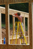 Nailing plywood. A worker nail up plywood on an addition Stock Image