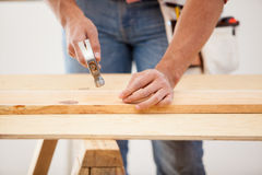 Nailing some wood boards. Closeup of a contractor using a hammer to nail a wood board in place Royalty Free Stock Photography