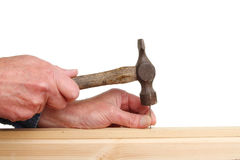 Nailing wood. Hands nailing two pieces of wood with an old tack hammer Stock Images