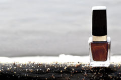 Nailpolish on a logg by the lake. A bottle of nail-polish on a log by the lake in a sunny day Stock Image
