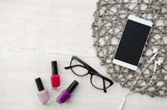 Nailpolishes, γυαλιά, τηλέφωνο και ακουστικά στον ξύλινο πίνακα Στοκ εικόνες με δικαίωμα ελεύθερης χρήσης