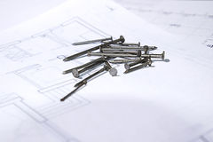 Nails. Photo of the nails on a house plan Royalty Free Stock Image