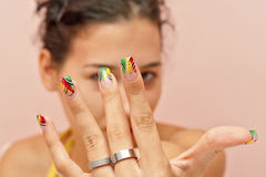 Nails. Girl is showing her manicured, crazy colored decorated nails. Rings are inevitable addition on woman's fingers Stock Photos