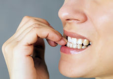 Nails biting. Nervous young woman biting her nails on gray background stock photography