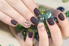 Nails with abstraction. Nails black and coffee color with abstraction Royalty Free Stock Photo