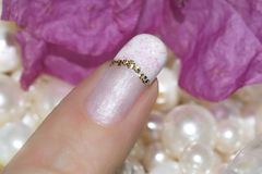 Nails with a French manicure with a gold stripe Stock Images