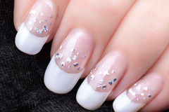 Nails with a French manicure and silver tinsel Stock Images
