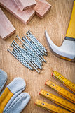 Nails glove planks hammer wooden ruller on wooden board Stock Photography