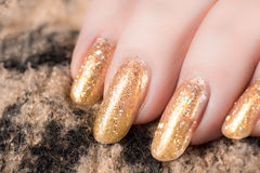 Nails in gold. Close up of nails with gold nail polish Royalty Free Stock Photography