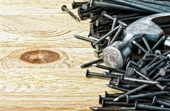 Nails and hammer on wooden background. Royalty Free Stock Image