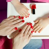 Nails on the hands of mother and daughter painted with red varnish.  royalty free stock image