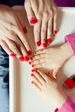Nails on the hands of mother and daughter painted with red varnish.  stock photo