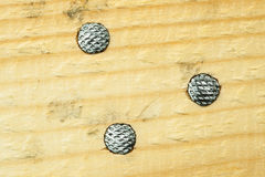 Nails. Heads in wood. Top view Royalty Free Stock Photo