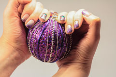 Nails lacquered in fun Christmas style. On the ring finger paint Stock Photography