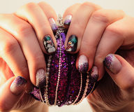 Nails lacquered in fun Christmas style. Stock Photos