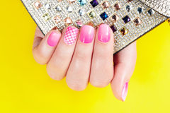 Nails with manicure covered with pink nail polish, yellow background Royalty Free Stock Photo