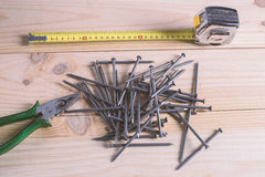 Nails, a measuring tape and pliers Stock Photo