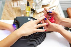Nails painting with UV dry lamp in blue light Royalty Free Stock Photo